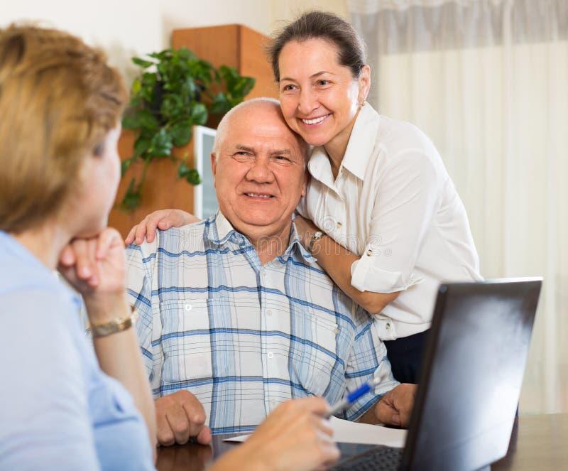 Coppie senior con l'assistente sociale a casa immagini stock libere da diritti