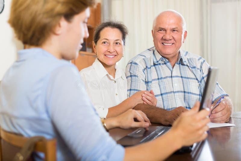 Coppie senior con l'assistente sociale a casa fotografia stock