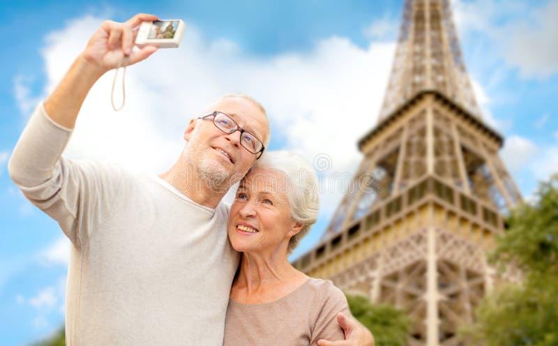 Coppie senior con la macchina fotografica sopra la torre Eiffel immagini stock