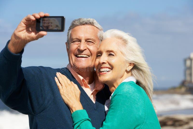 Coppie senior con la macchina fotografica sulla spiaggia immagine stock libera da diritti