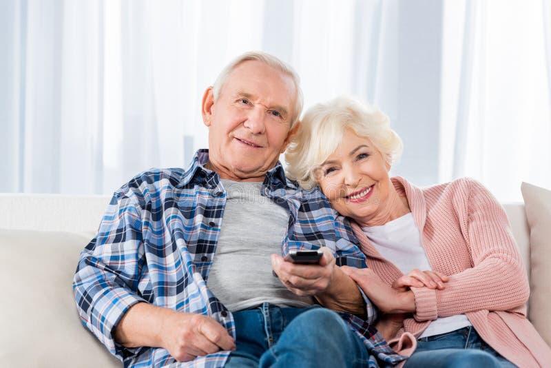 coppie senior con la TV di sorveglianza telecomandata immagine stock