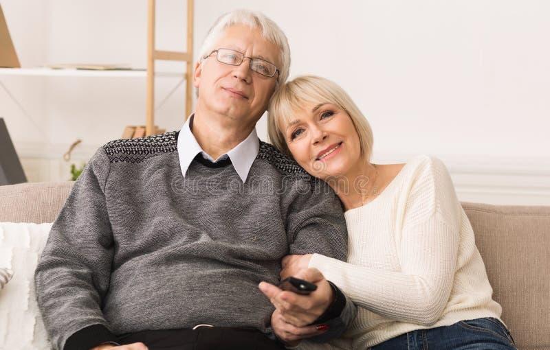 Coppie senior di amore che guardano TV con telecomando immagini stock