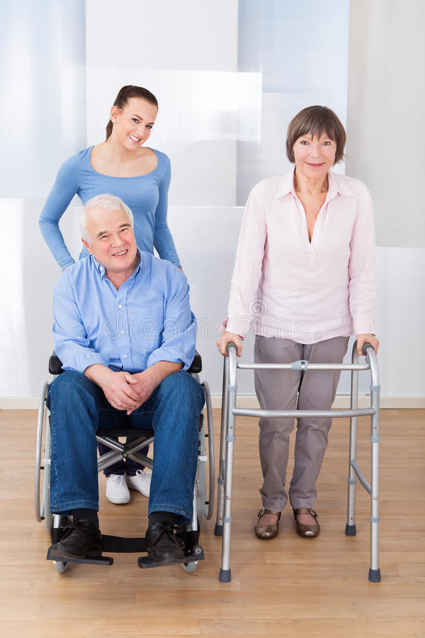 Coppie senior disabili con il badante fotografia stock libera da diritti