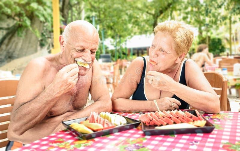 Coppie senior divertendosi mangiando la frutta di stagione in ristorante tailandese fotografia stock libera da diritti