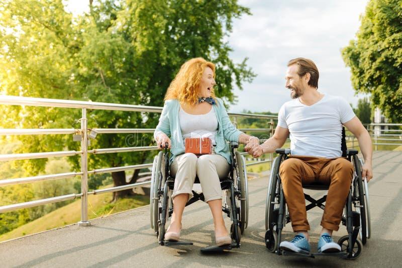 Coppie senior emozionali che riposano all'aperto nelle sedie a rotelle fotografia stock