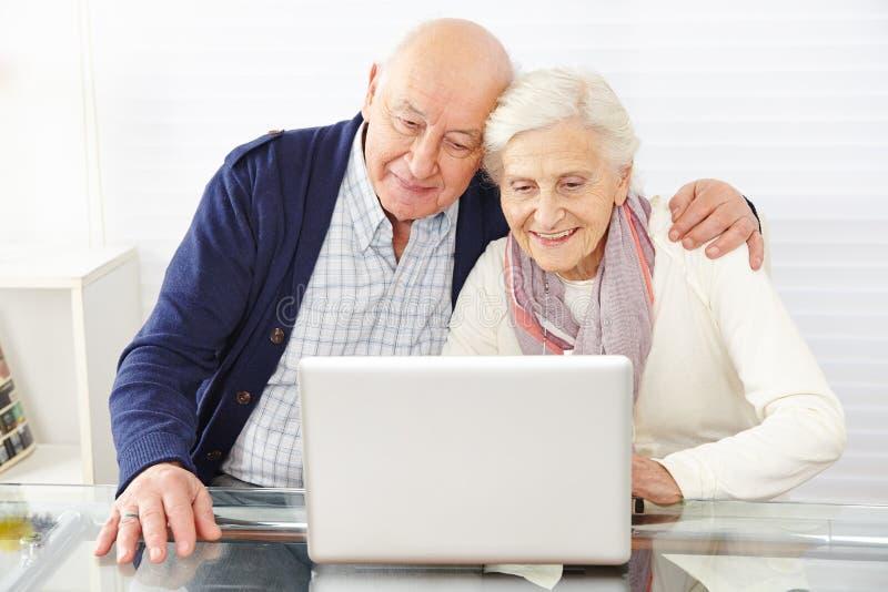 Coppie senior facendo uso del commercio elettronico fotografie stock