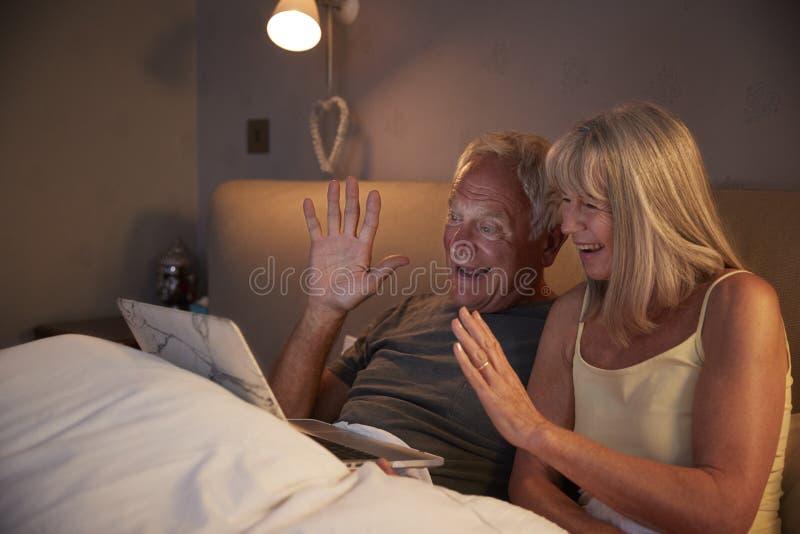 Coppie senior facendo uso del computer portatile da collegarsi con la famiglia per la video chiamata immagine stock libera da diritti