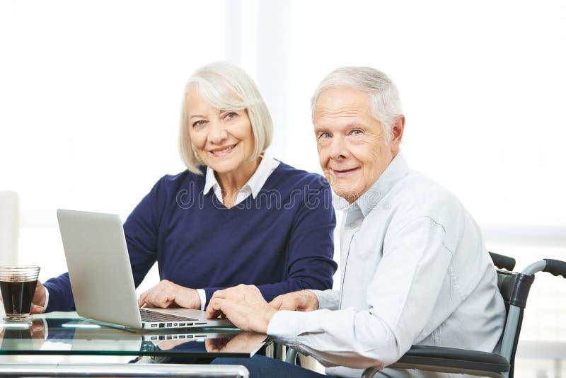 Coppie senior facendo uso di acquisto online di commercio elettronico immagine stock libera da diritti