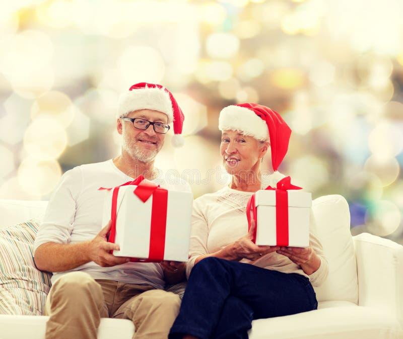 Coppie senior felici in cappelli di Santa con i contenitori di regalo immagini stock