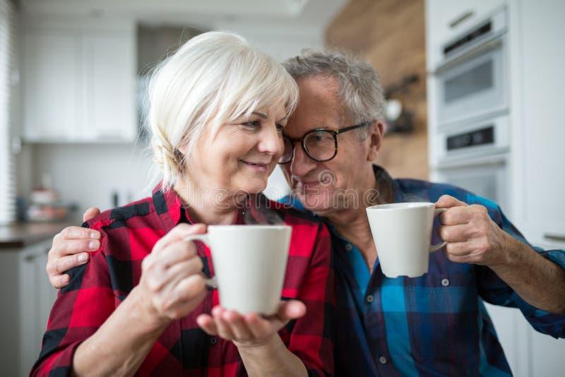 Coppie senior felici che mangiano il caffè di mattina insieme fotografia stock