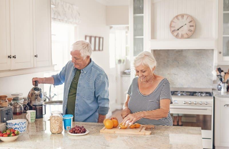 Coppie senior felici che preaparing una prima colazione sana nella loro cucina immagini stock libere da diritti