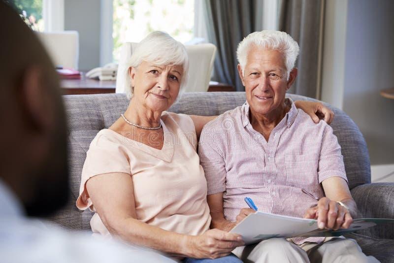 Coppie senior felici che prendono consiglio finanziario a casa fotografia stock libera da diritti