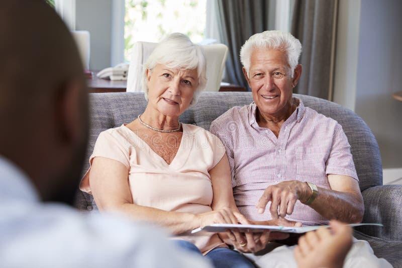 Coppie senior felici che prendono consiglio finanziario a casa fotografie stock libere da diritti