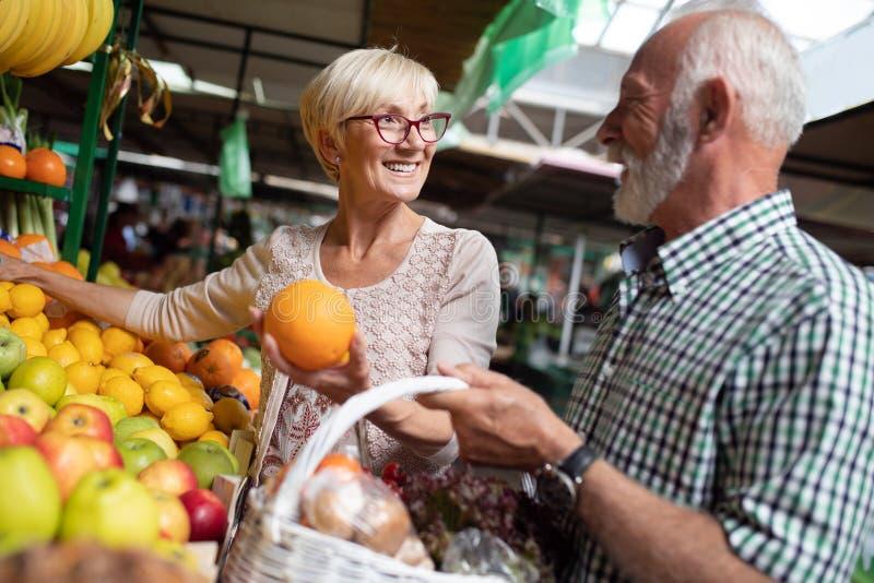 Coppie senior felici con il canestro al mercato locale fotografia stock