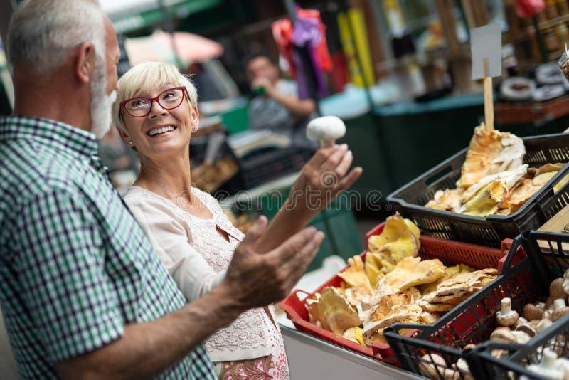 Coppie senior felici con il canestro al mercato locale immagine stock libera da diritti