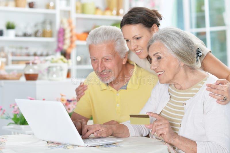 Coppie senior felici con la figlia adulta che per mezzo del computer portatile fotografia stock libera da diritti