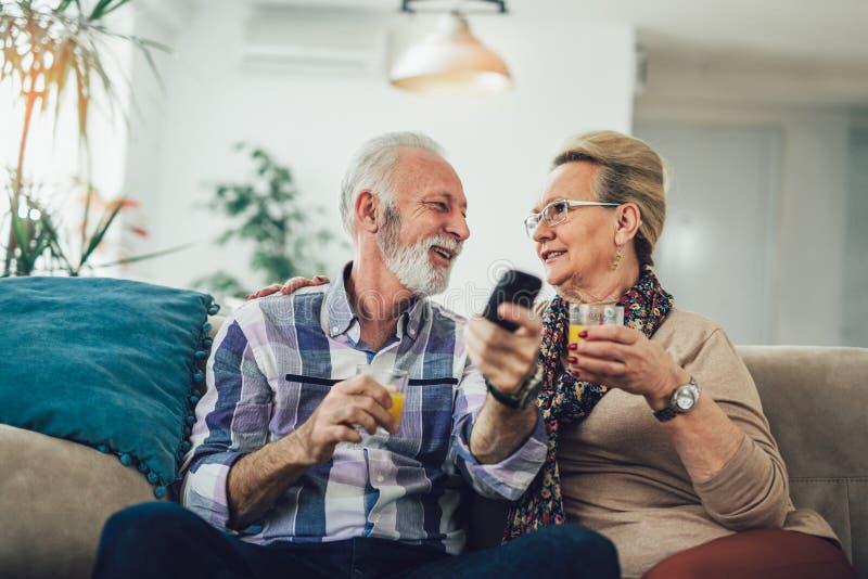 Coppie senior felici con la TV di sorveglianza telecomandata immagine stock libera da diritti