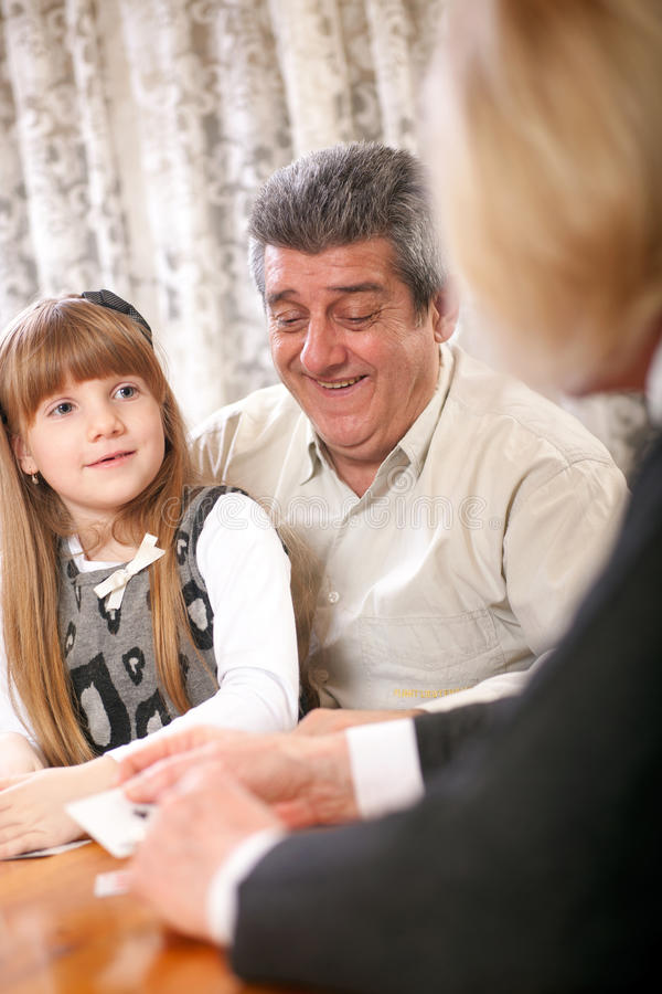 Coppie senior felici con le carte da gioco della nipote fotografia stock
