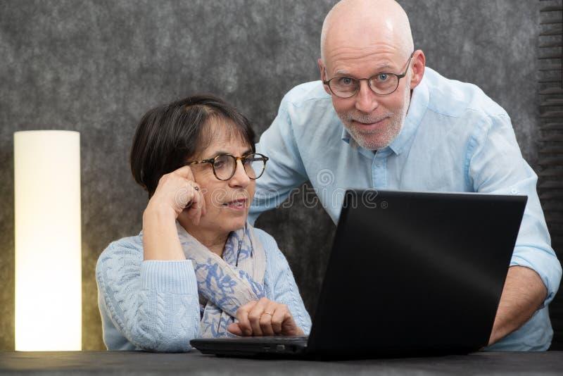 Coppie senior felici facendo uso del computer portatile a casa fotografia stock libera da diritti