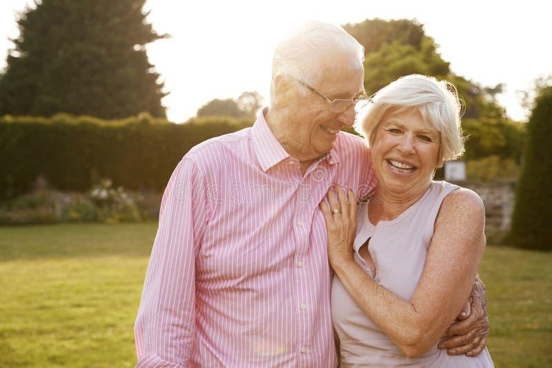 Coppie senior in giardino che sorride alla macchina fotografica, fine su immagini stock libere da diritti
