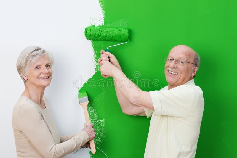 Coppie senior piacevoli che ostentano la nuova pittura immagini stock