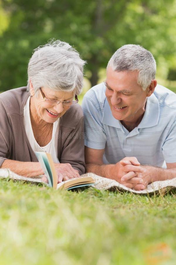 Coppie senior rilassate sorridenti che si trovano nel parco immagine stock libera da diritti