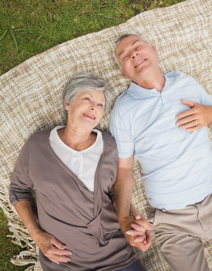 Coppie senior rilassate sorridenti che si trovano nel parco immagine stock