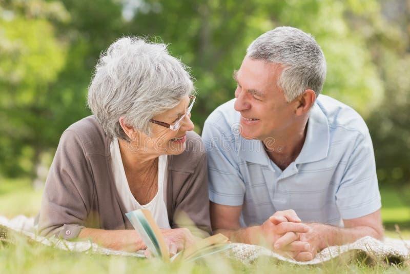 Coppie senior rilassate sorridenti che si trovano nel parco fotografie stock libere da diritti