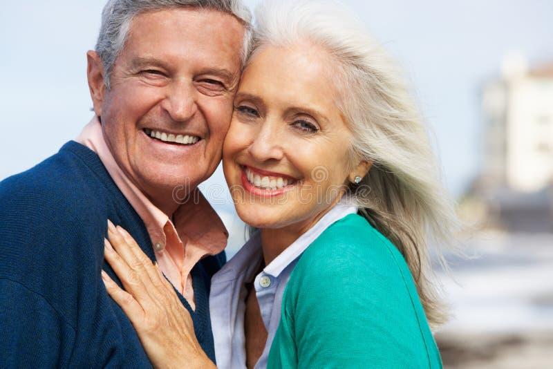 Coppie senior romantiche che abbracciano sulla spiaggia fotografia stock