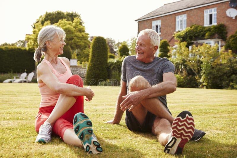 Coppie senior sane che si esercitano insieme nel giardino immagine stock libera da diritti