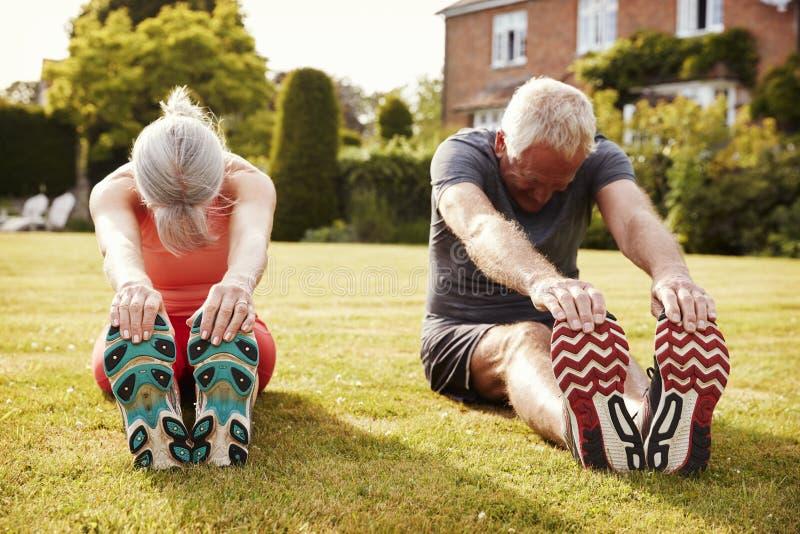 Coppie senior sane che si esercitano insieme nel giardino fotografia stock libera da diritti