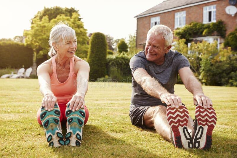 Coppie senior sane che si esercitano insieme nel giardino immagini stock