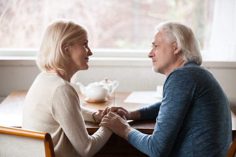 Coppie senior sensuali che si tengono per mano sguardo negli occhi fotografie stock libere da diritti