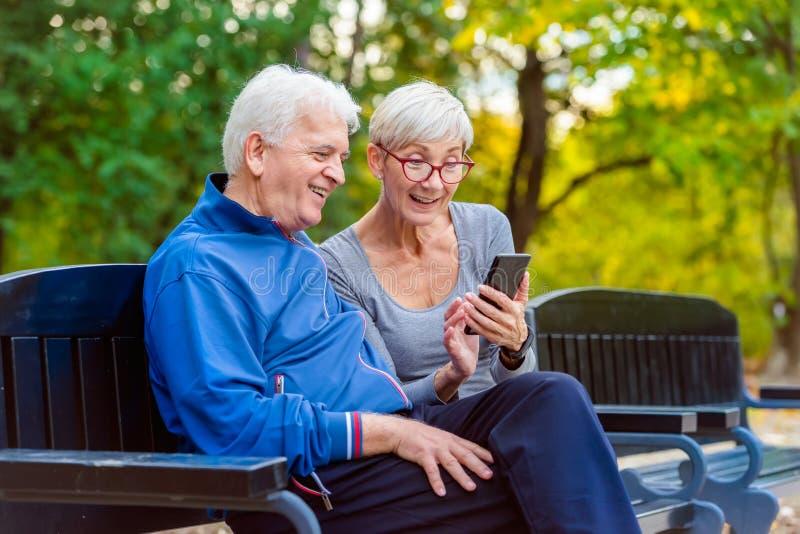 Coppie senior sorridenti che pareggiano nel parco facendo uso dello smartphone fotografia stock libera da diritti