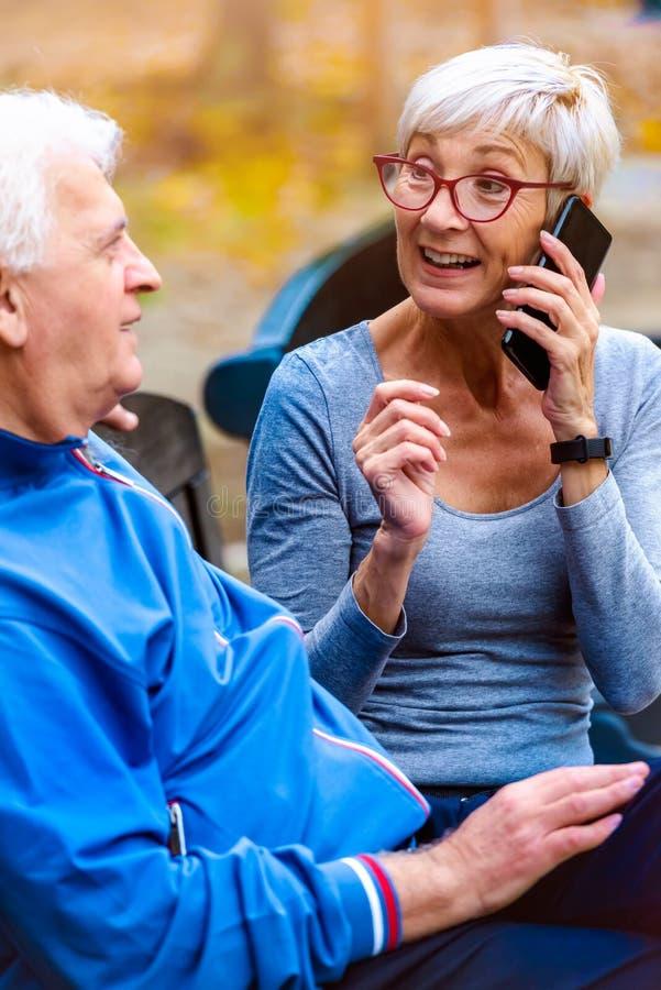 Coppie senior sorridenti che pareggiano nel parco facendo uso dello smartphone immagini stock