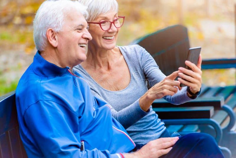 Coppie senior sorridenti che pareggiano nel parco facendo uso dello smartphone fotografia stock