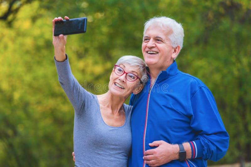 Coppie senior sorridenti che pareggiano nel parco che prende selfie immagini stock