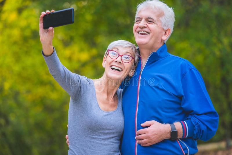 Coppie senior sorridenti che pareggiano nel parco che prende selfie fotografia stock