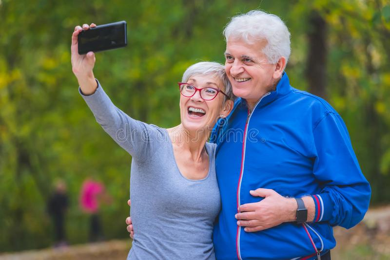 Coppie senior sorridenti che pareggiano nel parco che prende selfie fotografie stock