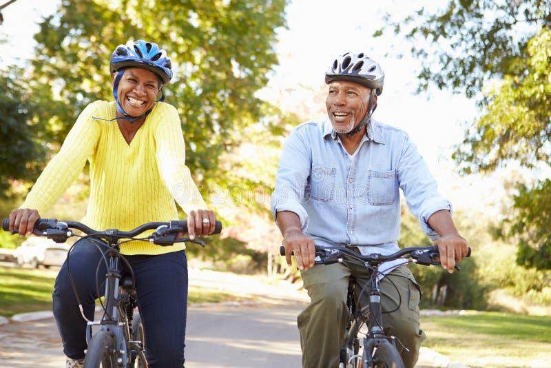 Coppie senior sul giro del ciclo in campagna fotografie stock libere da diritti