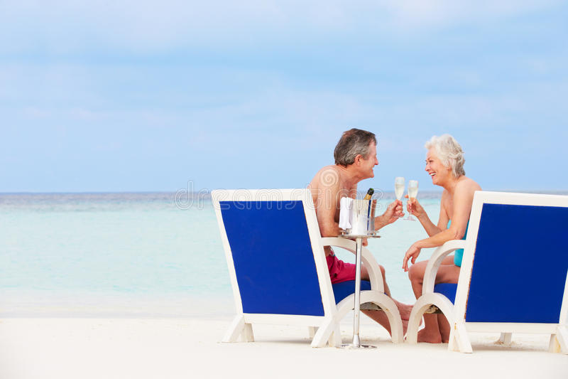 Coppie senior sulla spiaggia che si rilassa nelle sedie che bevono Champagne fotografia stock