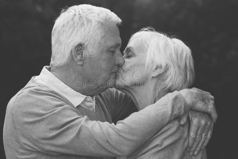 Coppie senior sveglie che baciano calorosamente all'aperto fotografia stock