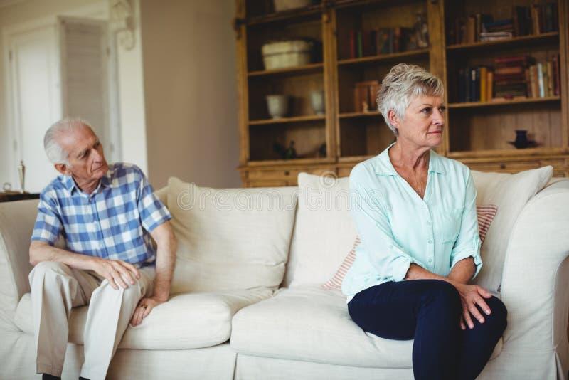 Coppie senior turbate che si rilassano sul sofà fotografie stock