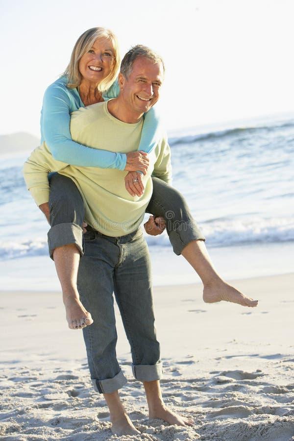 Coppie senior in vacanza con il marito che dà a due vie della moglie immagini stock libere da diritti