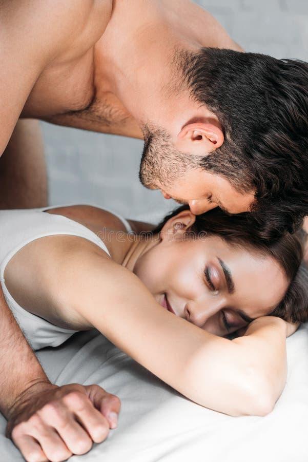 coppie sensuali degli amanti che si trovano sul letto immagini stock
