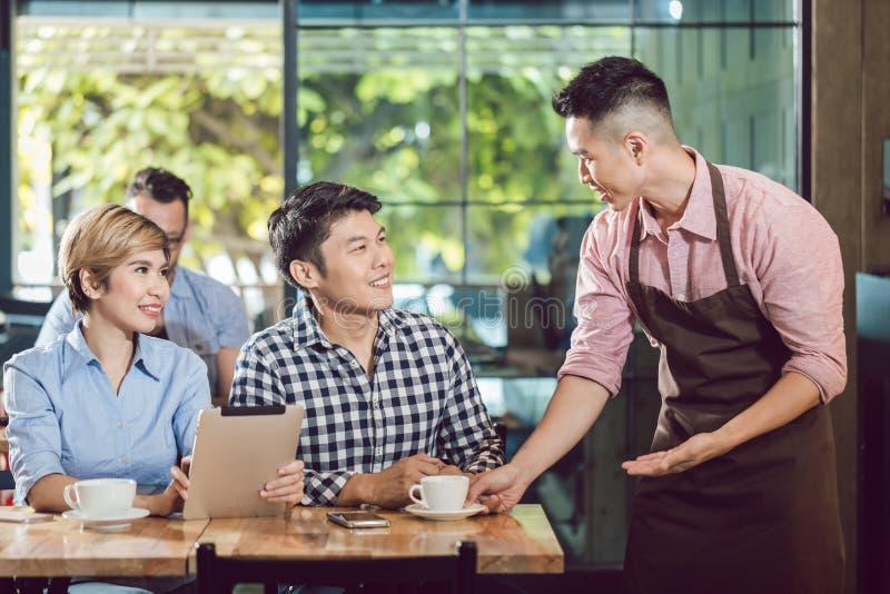 Coppie serventi del cameriere felice immagini stock libere da diritti