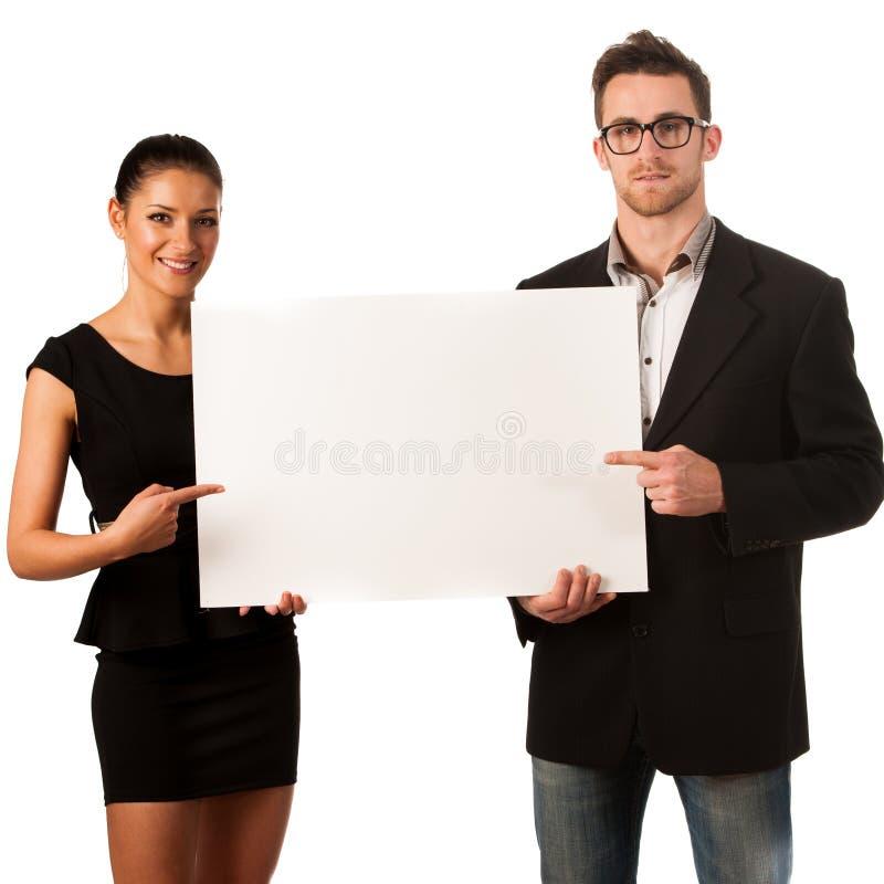 Coppie sicure di affari che stanno accanto ad un grande bordo in bianco a immagini stock