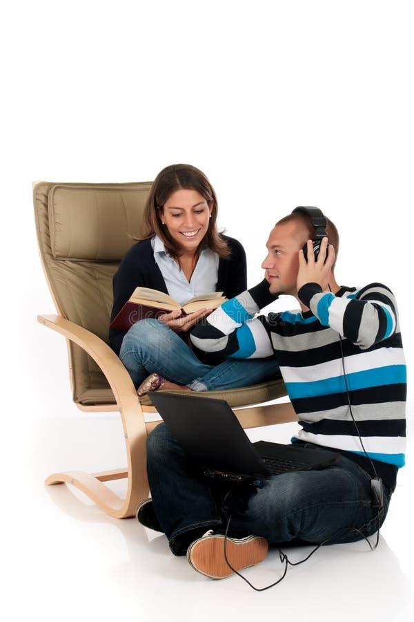 Coppie, sofà del computer portatile del libro immagine stock