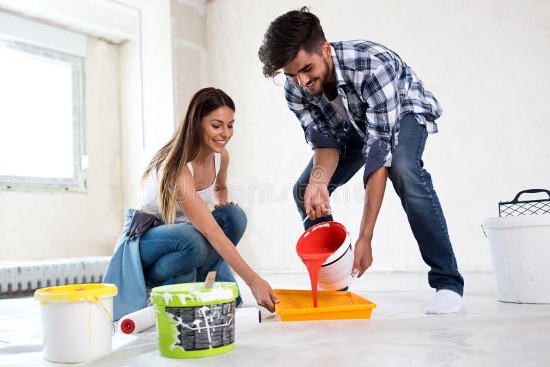 Coppie sorridenti adorabili che dipingono nuova casa, rinnovamento della nuova casa fotografia stock