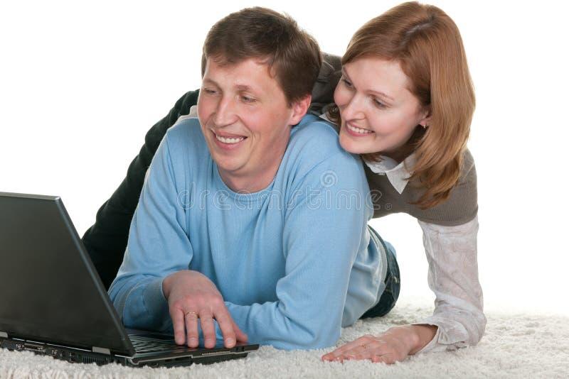 Coppie sorridenti al computer portatile immagine stock libera da diritti